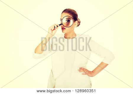 Businesswoman looking into a magnifier and have a big eye
