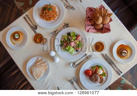 Formal table setting in the fine dining restaurant. International cuisine spread. View from top.