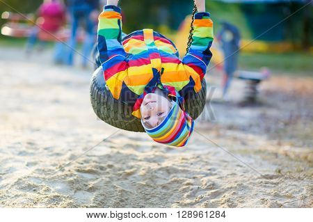 Preschool little kid boy having fun with chain swing on outdoor playground. child swinging on warm sunny spring or autumn day. Active leisure with kids. Boy wearing colorful clothes