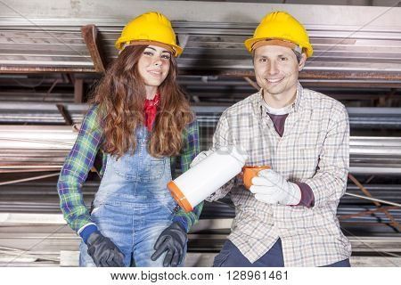 Portrait Of Young Couple Of Workers On Coffee Break In A Steel Mill