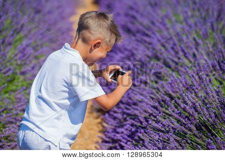 Happy boy take photo in lavender summer field near Valensole. Provence, France.