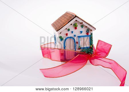 House tied with a red ribbon on a white background