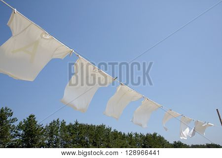 White t-shirts hanging to dry on a clothesline