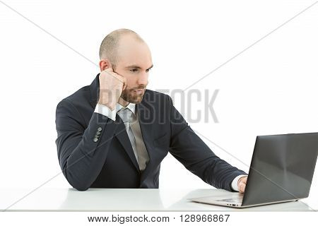Caucasian business man concentrated working on his laptop. Isolated on white background.