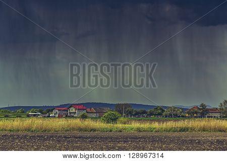 Cloudburst over a village and farmlands during spring in Transylvania region Romania.