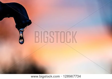 Drop of water coming out of a metal tap with a soft background