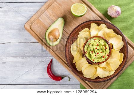 bowl of guacamole dip and potato chips on a clay brown dish on a green table mat with slice of lime and avocado on a white wooden backgroundtop view