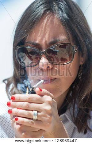 Close-up of adult woman in sunglasses lighting up the cigarette in sunlight