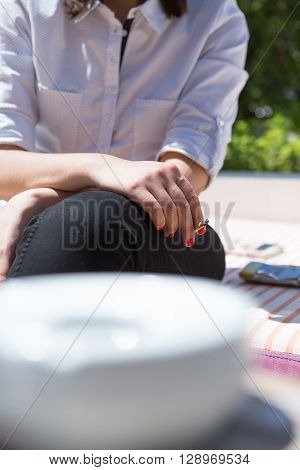 Unrecognizable woman smoking cigarette while sitting outdoor