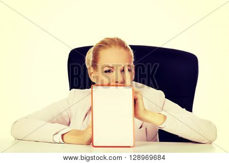 Young business woman sitting behind the desk and holding a board with ban