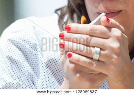 Close-up of unrecognizable woman lightning up the cigarette with lighter
