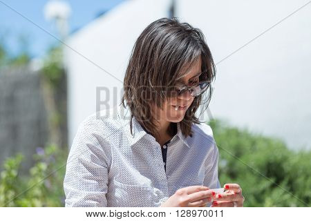 Adult brunette rolling paper while holding filter in mouth