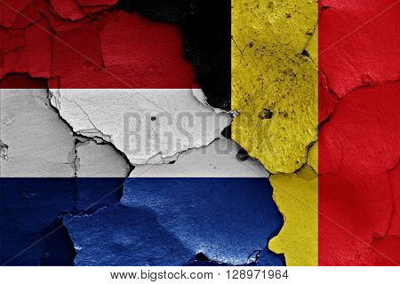flags of Netherlands and Belgium painted on cracked wall