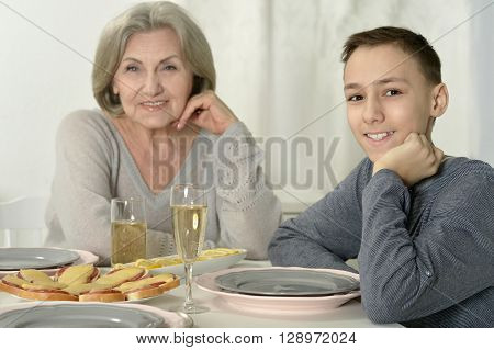 portrait of  cute grandmother  with kid at dinner