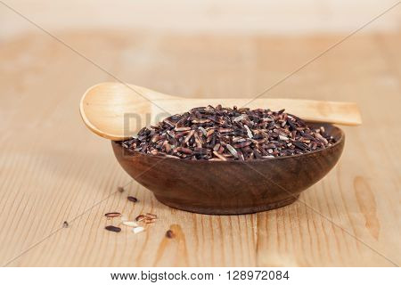 raw Rice berry in wood bowl background