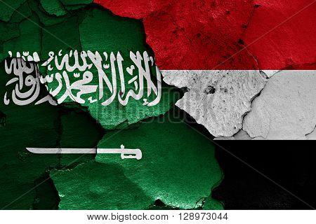 flags of Saudi Arabia and Yemen painted on cracked wall