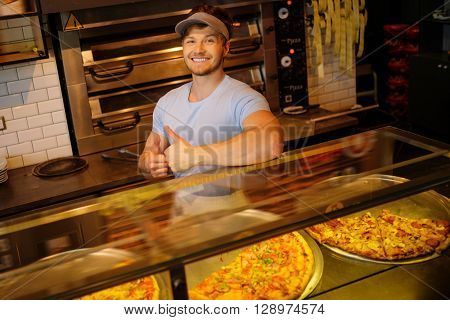 Handsome pizzaiolo standing at kitchen in pizzeria.