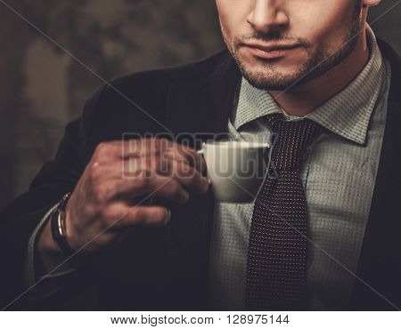 Serious well-dressed hispanic man with cup of coffee posing on dark background.