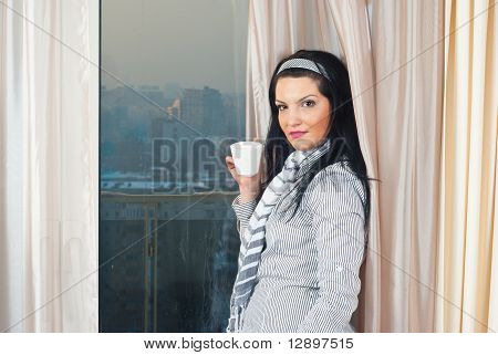 Woman With Cup In Front Of Window