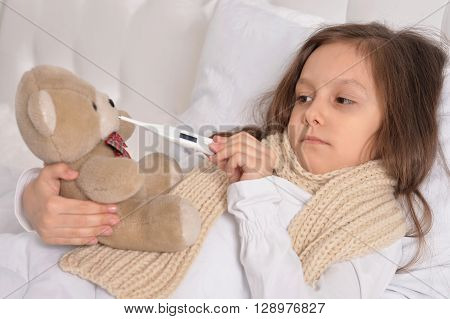 Sad sick little girl lying in the bed with teddy bear toy