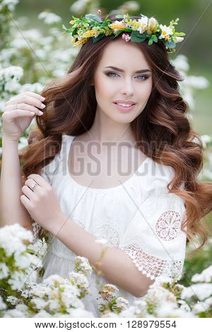 Spring portrait of a beautiful woman in a wreath of flowers,long curly red hair,gray eyes,light makeup and a beautiful smile,dressed in a white summer dress posing near the Bush of a blossoming white flowers outdoors in the spring