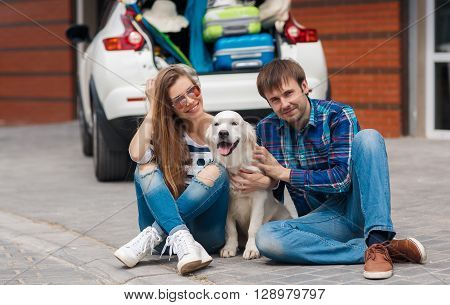 Happy young couple,woman with long hair,sun glasses,striped t-shirt and blue jeans and the dark hair man in blue plaid shirt and blue jeans,sitting with his friend,a dog breed Golden Retriever,near a white car loaded with suitcases before you travel