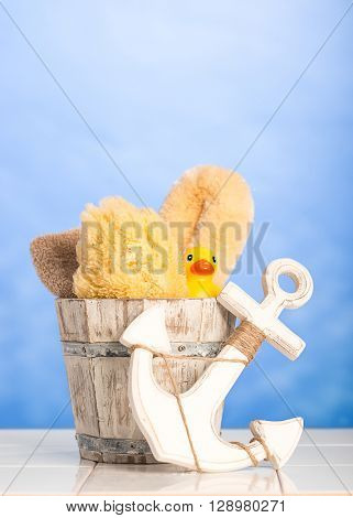 Bathroom items in wooden tub with decorative anchor