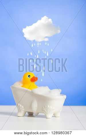 Rubber duck taking a bath with cloud over head