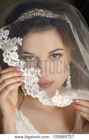 The young beautiful woman, the brunette with a wedding hairdress and a professional make-up, in ears expensive earrings, is dressed in a white wedding dress and a transparent white veil, waits for the groom in a hotel room