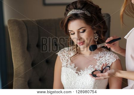 Beautiful young bride with curly brunette hair,beautiful wedding hairstyle with tiara,large earrings,white wedding dress,a gentle smile,sitting on a high chair in the hotel room, the make-up, using the services of a makeup artist