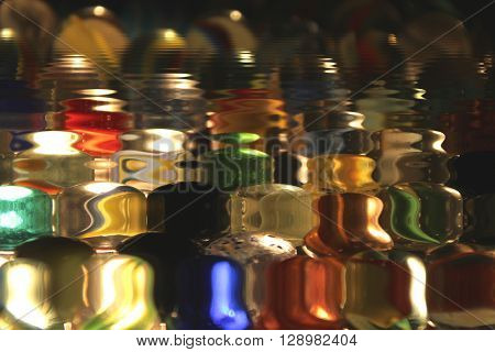 a very close up of multicolored balls reflecting in the water