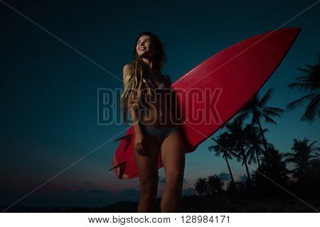 Pensive young woman in swimsuit walking on the beach with surfboard in sunset