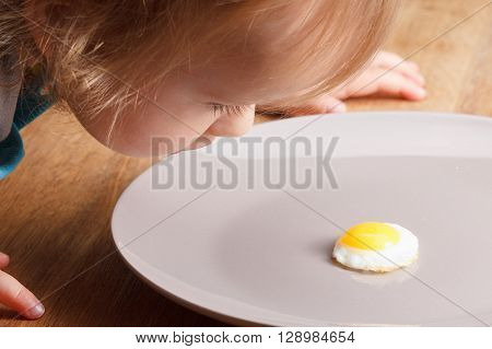 Caucasian child looking at a small breakfast omelette