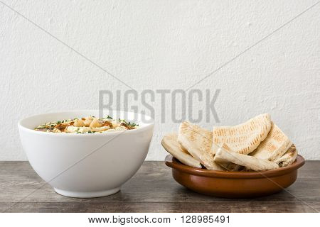 Homemade hummus and pita bread on rustic wood