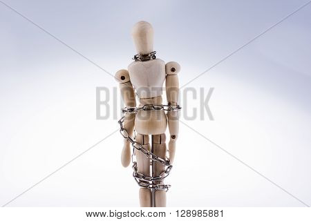 Wooden model man in chains on a white background