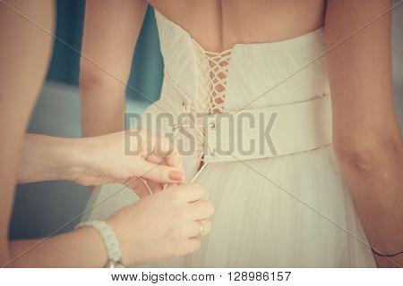 Bridesmaid tying bow on wedding dress, close-up
