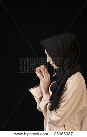 portrait in profile Beautiful Muslim girl in a black scarf on her head on a black background. Ufa