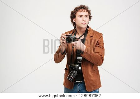 Male reporter holding camera and looking away isolated on a white background