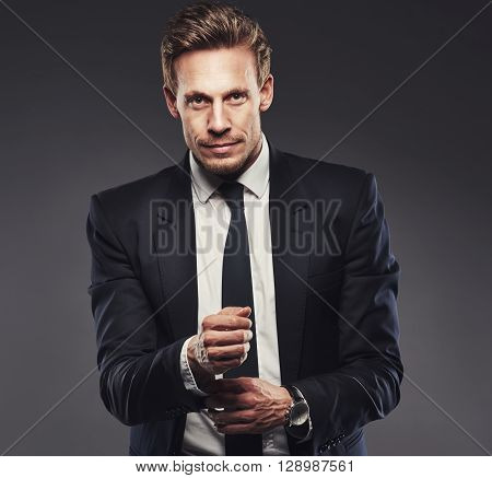 Pensive Attractive Businessman Adjusting His Cuff
