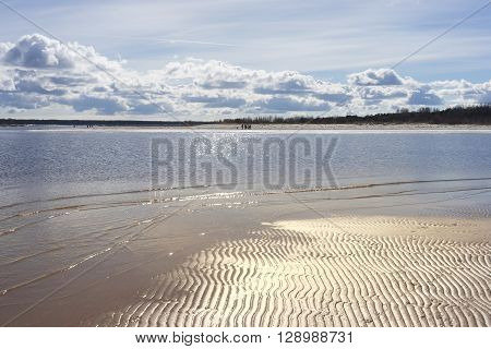 People walk along the sandy bank of the river with the reflections on the water on a sunny spring day
