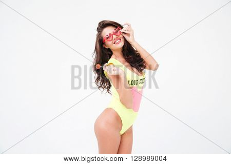 Sexy woman in bodysuit holding candy and looking at camera isolated on a white background