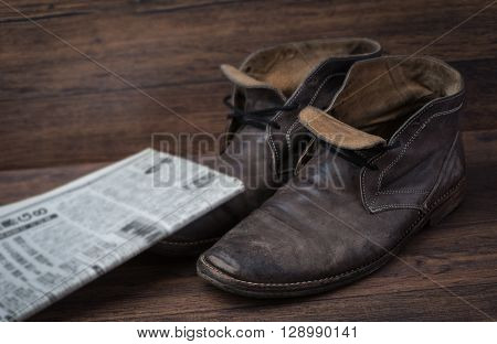 Old Worn Out Brown Leather Shoes With Newspaper Over The Dark Background