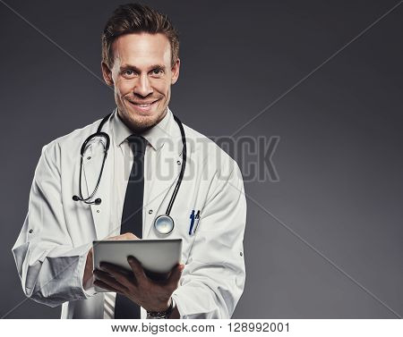 Smiling Doctor With Stethoscope And Tablet