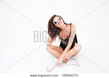 Stylish woman in sunglasses sitting on the floor isolated on a white background
