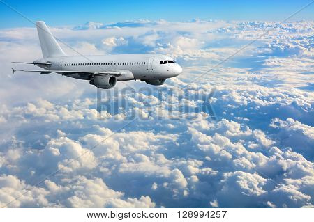 Commercial passenger plane flying high above clouds