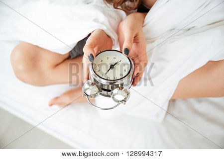 Closeup portrait of a female hands holding alarm clock on the bed