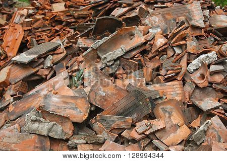 Pile of debris of a destroyed building, mostly roof tiles