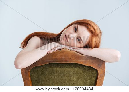 Relaxed redhead woman sitting on the chair and looking at camera isolated on a white background