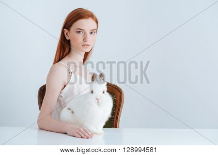 Young redhead woman sitting at the table with rabbit and looking at camera isolated on a white background