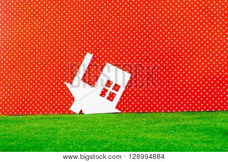Paper house upside down on a white-dotted red background with grass
